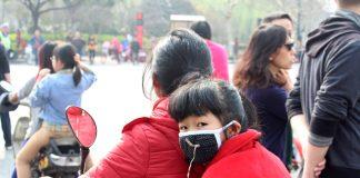 Jente med munnbind i den kinesiske byen Hangzhou.