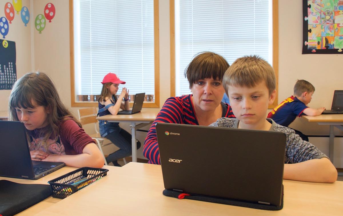 Tea Elise Magnussen (7) og Isak Tisthamar (7) får hjelp av Linda Petterteig med dei nye chromebookane deira. Foto: Svein Olav B. Langåker