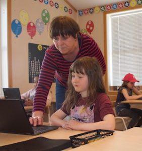 Lærar Linda Petterteig hjelper Tea Elise Magnussen med oppgåvene.