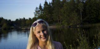 Silje Solvang smiler med solbriller på hovudet, med eit vatn i bakgrunnen.